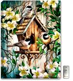 Three pudgy spring chickadee birds sit around a rustic birdhouse, with cream and white flowering vines surrounding them.