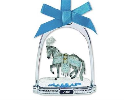 "Breyer's 2018 Stirrup Ornament features a finely-detailed miniature of the 2018 Holiday Horse, ""Celestine."" She is framed inside a classic silver-tone stirrup that has a crystal snowflake dangling from its top. This glittering ornament hangs from a blue r"