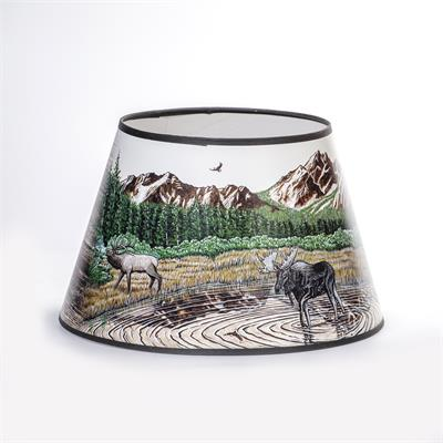 Rustic Mountain Scene with lake, Elk, and Moose  Bring mountain flair to your Aladdin table lamp. This exclusive parchment shade features artwork by renowned local artist Dennis Lipp, perfect for adding a touch of décor to your home. Plus, it helps diffus