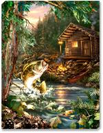 A large spotted bass leaps out of the mountainside creek to catch a dragonfly. A tiny log cabin sits in the background, complete with red canoe, stone fireplace, lantern, and campfire. The mountains behind the cabin are filled with lush evergreen trees.