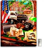 A 1950s black and white police car is parked on main street, in front of City Hall and Main Street Deli. Inside the police station sits a black hat, classic typewriter, rotary telephone, and case files.